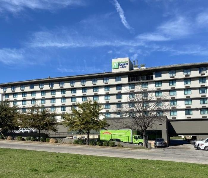 A lime green SERVPRO truck is parked out front of a large beige hotel.